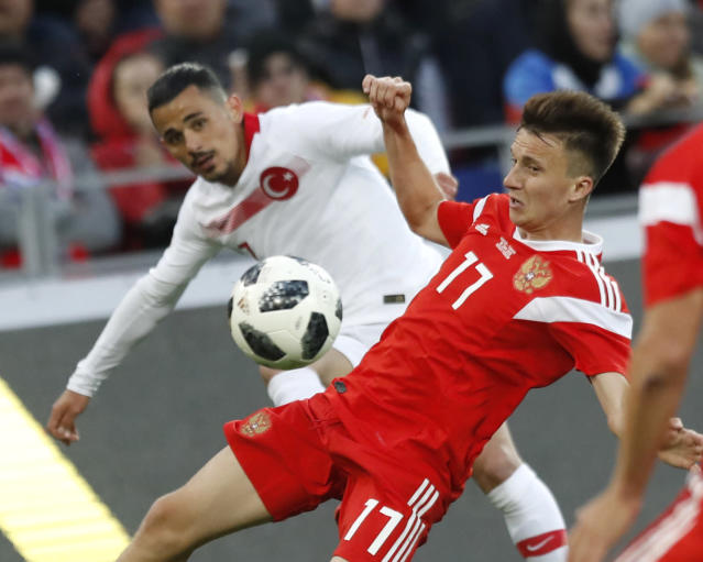 Turkey's Serdar Gurler, left, battles for the ball with Russia's Aleksandr Golovin during a friendly soccer match between Russia and Turkey at the VEB Arena stadium in Moscow, Russia, Tuesday, June 5, 2018. (AP Photo/Pavel Golovkin)