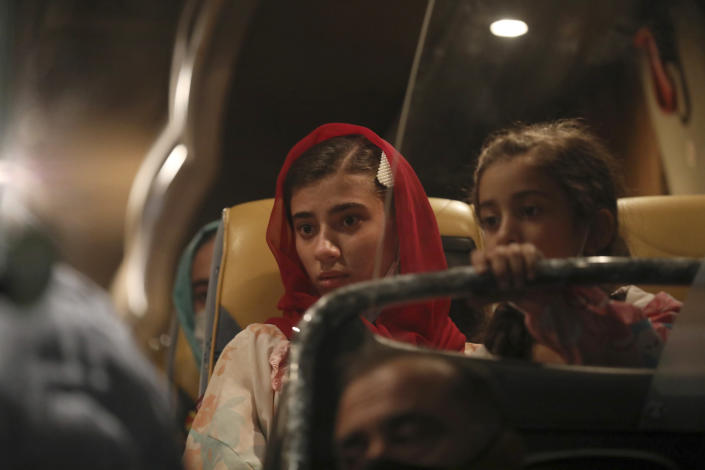 Afghan evacuees from Afghanistan sit in a bus after the arrival of the second flight with 95 passengers at the International Airport in Tirana, Albania, Friday, Aug. 27, 2021. Albania on Friday housed its first group of Afghan evacuees who made it out of their country despite days of chaos near the Kabul airport, including an attack claimed by the Islamic State group. (AP Photo/Franc Zhurda)