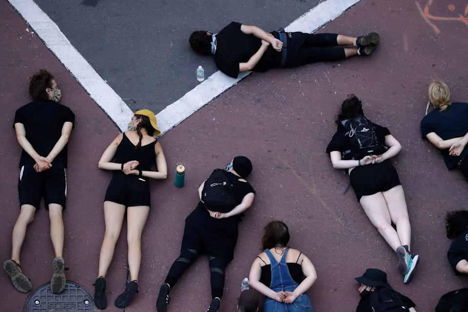 Protesters demanding police reforms and an end to Operation Legend lie in the street to block a downtown Kansas City, Missouri, intersection July 17, 2020.