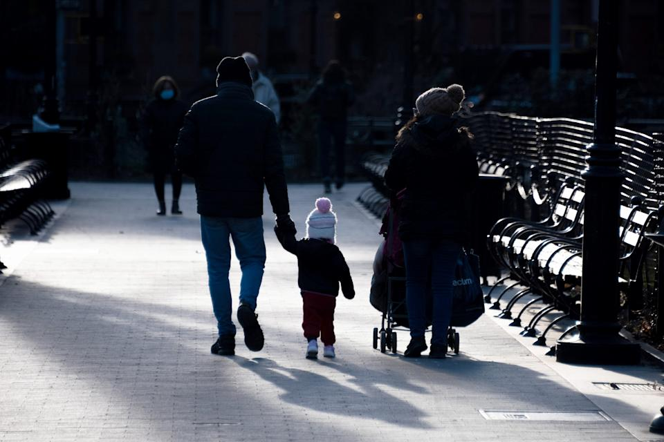 NEW YORK, NEW YORK - MARCH 15: A father holding his child's hand walks next to his mother while casting shadows in Washington Square Park on March 15, 2021 in New York City. After undergoing various shutdown orders for the past 12 months the city is currently in phase 4 of its reopening plan, allowing for the reopening of low-risk outdoor activities, movie and television productions, indoor dining as well as the opening of movie theaters, all with capacity restrictions. (Photo by Alexi Rosenfeld/Getty Images)