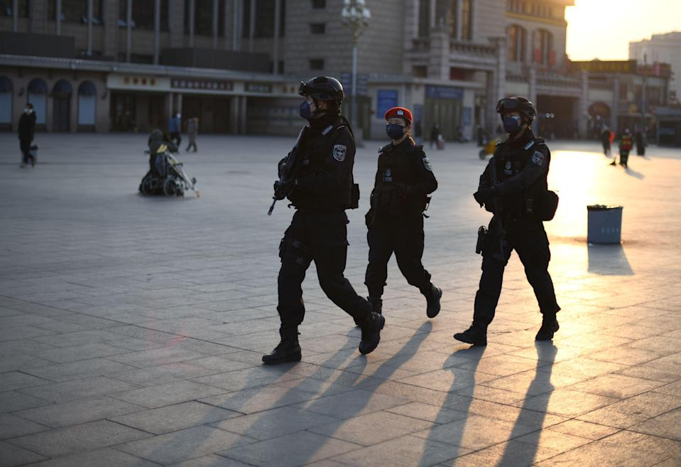 Policemen, wearing protective facemasks, patrols around Beijing Railway Station on 30 January, 2020. A knife attack in the city of Kaiyuan in Liaoning province has left seven dead, according to state media. (AFP via Getty Images)