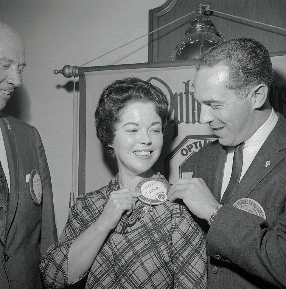 """<p>Shirley Temple Black receives an """"Optimist button"""" from Dr. Kenneth C. Stergion, after appearing at an Optimist Club luncheon. Temple was a Republican candidate in a special election for the 11th congressional district in CA.</p>"""