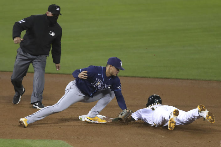 Oakland Athletics' Elvis Andrus, right, is tagged out by Tampa Bay Rays' Willy Adames on a steal attempt during the seventh inning of a baseball game in Oakland, Calif., Friday, May 7, 2021. (AP Photo/Jed Jacobsohn)