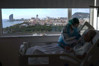 "Ana Aguilar, 20, a nursing assistant, feeds one of her patients at the COVID-19 ward at the hospital del Mar in Barcelona, Spain, Wednesday, Nov. 18, 2020. Aguilar asked one of her patients, who was in the last days of her life, if there was anything she could do for her. Her patient said she wanted to eat ""salmorejo,"" a traditional kind of creamy tomato soup, so Aguilar made it at home and took it into the hospital. The patient said, ""tasty, tasty, tasty,"" after each spoonful as she ate it. (AP Photo/Emilio Morenatti)"