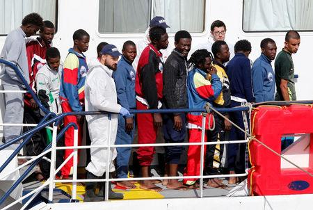 Migrants wait to disembark from MOAS vessel Phoenix in the Sicilian harbour of Catania
