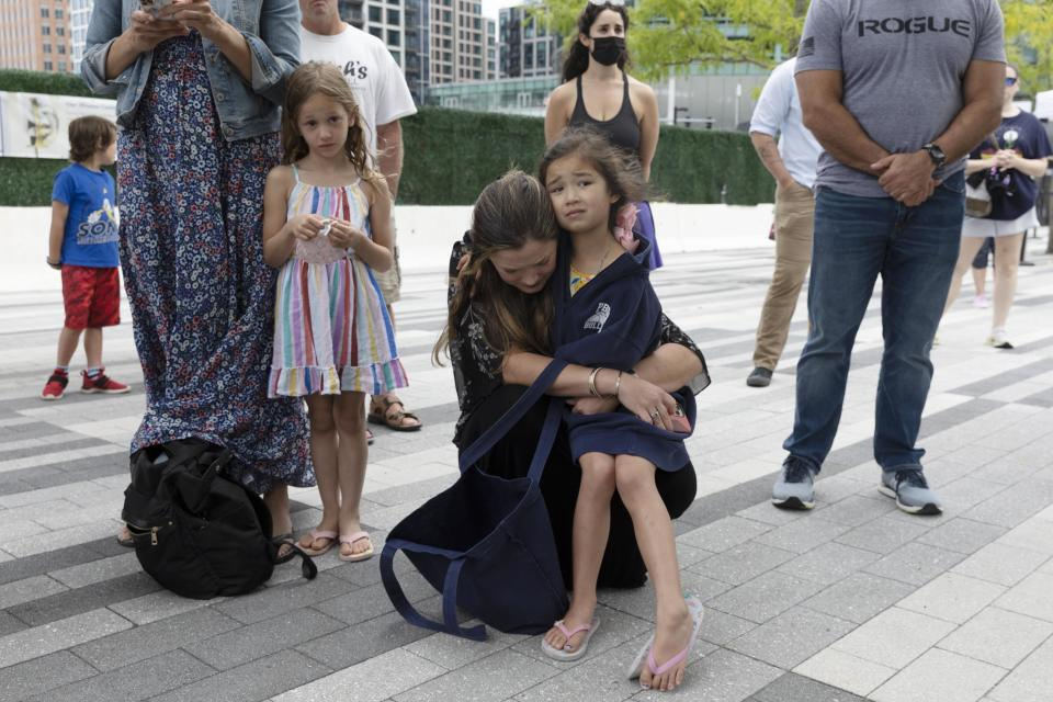 Ingrid Hammond, center, hugs her daughter Brigit during a ceremony at the Massachusetts Fallen Heroes Memorial, Saturday, Aug. 28, 2021, in Boston. People gathered at the memorial to honor the U.S. service members killed in a suicide bombing at the airport in Kabul, Afghanistan, including Marine Sgt. Johanny Rosario Pichardo from Lawrence, Mass. (AP Photo/Michael Dwyer)