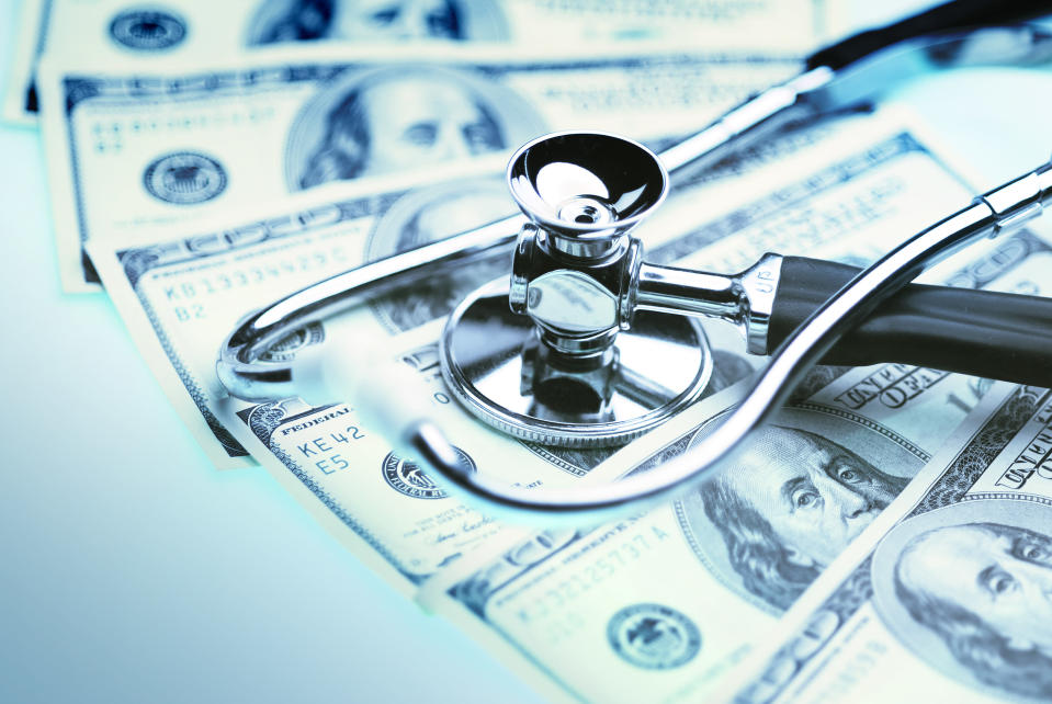 A stethoscope lies on top of fanned-out hundred-dollar bills.