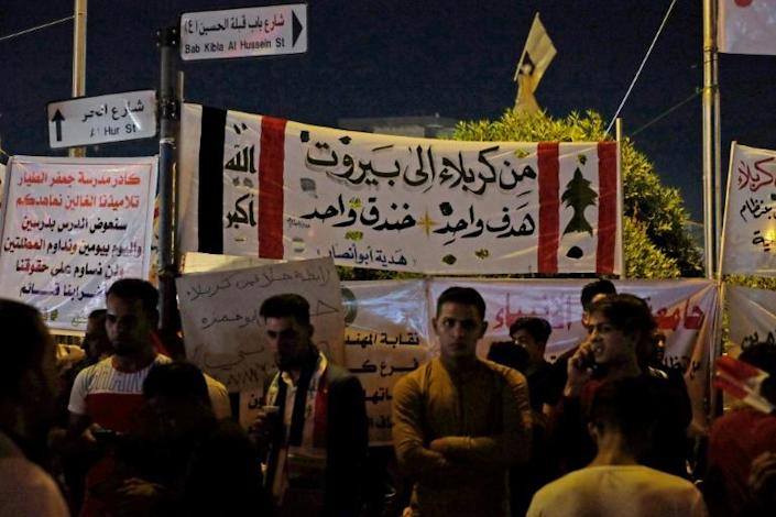 """Iraqi protesters stand under a banner reading """"From Karbala to Beirut, one goal, one trench"""" (AFP Photo/Mohammed SAWAF)"""