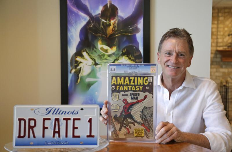 This Nov. 13, 2013, photo shows Steve Landman with one of his collectable comic books, a vanity license plate with the name of a childhood superhero on it, and a poster of the same superhero Dr. Fate, at his home in Kildeer, Ill. Diagnosed with Anti-MAG IgM Peripheral Neuropathy, a rare autoimmune disease that attacks the nervous system, Landman has for months watched helplessly as the numbness that started in his toes crawls up his legs to the point where he now moves as if trudging in snow. As he tries to sell his dental practice years before he thought he would, he's jumped back into his collection of 10,000 comics selling 420 of them in an online auction that could bring in over $750,000 for his family and more importantly, bringing awareness and recognition to the disease that is robbing him of his mobility, and profession. (AP Photo/M. Spencer Green)