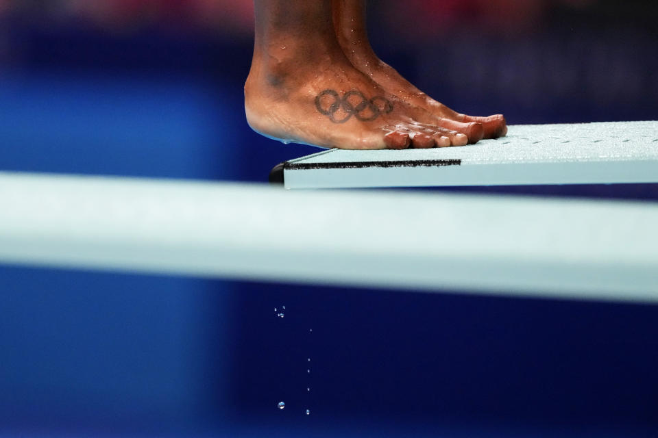 A tattoo of the Olympic rings decorate the foot of Jennifer Abel, of Canada, as she prepares to dive in the women's diving 3-meter springboard preliminary at the 2020 Summer Olympics, Friday, July 30, 2021, in Tokyo. (AP Photo/David Goldman)