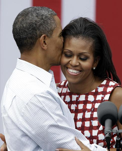 FILE - In this Aug. 15, 2012, file photo President Barack Obama kisses first lady Michelle Obama as they speak at a campaign event in Dubuque, Iowa. The first couple have have been frequently sharing personal tidbits on the campaign trail, seeking to remind people of one big reason they voted for Obama in the first place: most people like him personally. Obama talks about his single mother's struggles, tells voters he misses his wife when they're apart, and she tells voters he's still cute, even with gray hair. (AP Photo/Charlie Neibergall, File)