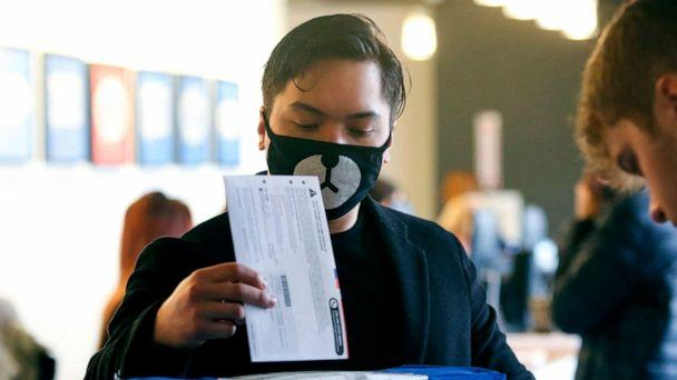 PHOTO: Matthew Guerrero, 22, of Des Moines, Washington wears a bear mask as he drops off his presidential primary mail-in ballot in person at King County Elections in Renton, Washington, March 10, 2020. (Jason Redmond/AFP via Getty Images)