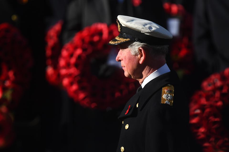 The Prince of Wales laid the first wreath on behalf of the Queen, who watched the service from a nearby balcony (Picture: SWNS)