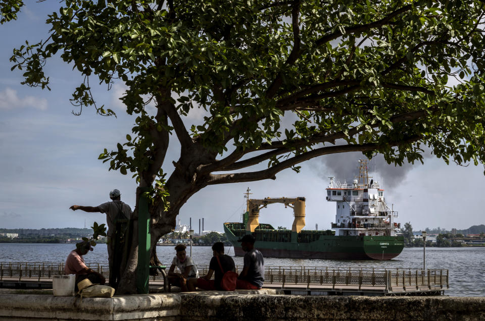 "Fishermen sit in the shade as the ""Carmita"" cargo ship, flying a Panamanian flag, navigates the bay of Havana, Cuba, Thursday, Oct. 22, 2020. Cuba's foreign minister presented the nation's report on the impact of the U.S. embargo over the past year on Thursday. (AP Photo/Ramon Espinosa)"