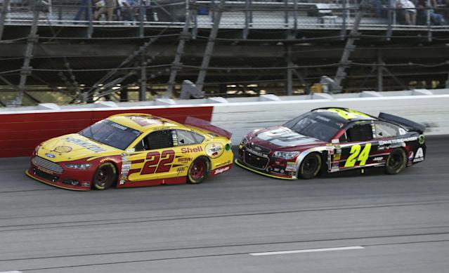 Joey Logano (22) races Jeff Gordon (24) during the NASCAR Sprint Cup auto race at Darlington Speedway in Darlington, S.C., Saturday, April 12, 2014. (AP Photo/Chuck Burton)