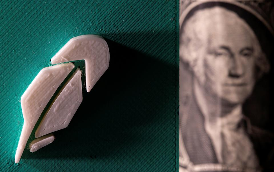 3D-printed Robinhood logo is seen in front of U.S. dollar banknote in this illustration taken, July 1, 2021. REUTERS/Dado Ruvic