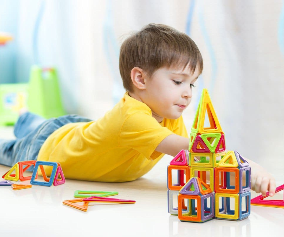 A brown haired child plays on the floor building a tower out of colourful magnetic shapes.