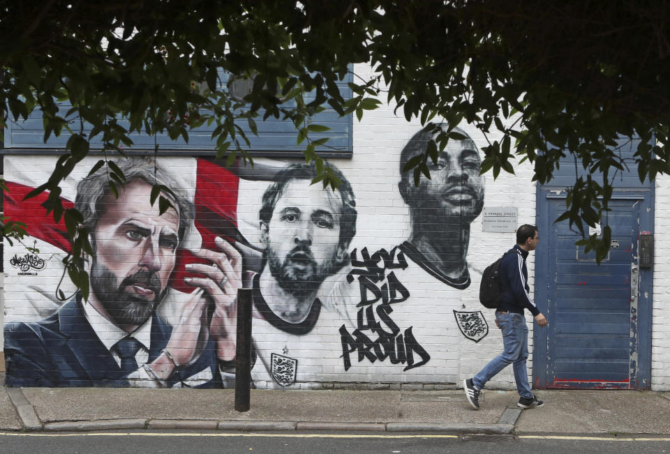 A man walks past a mural depicting England's manager Gareth Southgate, captain Harry Kane and Raheem Sterling, from left, painted on a wall near Vinegar Yard in south London, Wednesday July 14, 2021. England lost the Euro 2020 soccer championship final match to Italy on Sunday July 11. (AP Photo/Tony Hicks)