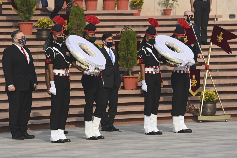 U.S. Secretary of State Mike Pompeo, left, and Secretary of Defence Mark Esper arrive to pay their tributes at the National War Memorial in New Delhi, India, Tuesday, Oct. 27, 2020. In talks on Tuesday with their Indian counterparts, Pompeo and Esper are to sign an agreement expanding military satellite information sharing and highlight strategic cooperation between Washington and New Delhi with an eye toward countering China. (Jewel Samad/Pool via AP)