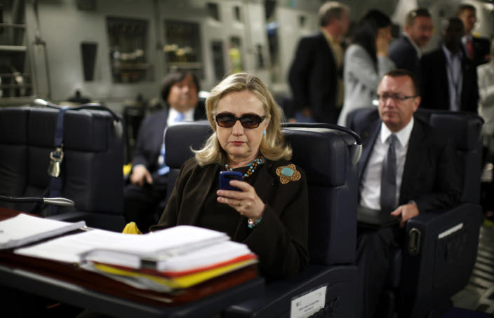 <p>Secretary of State Hillary Clinton checks her mobile device aboard a military C-17 plane from Malta bound for Tripoli, Libya, in October 2011. (Photo: Kevin Lamarque/Reuters)</p>