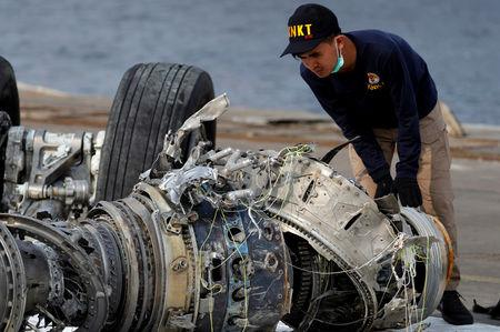 An Indonesian National Transportation Safety Commission official examines a turbine engine from the Lion Air flight JT610 at Tanjung Priok port in Jakarta
