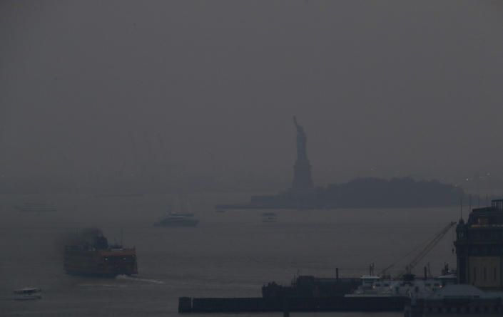 The Staten Island Ferry departs from the Manhattan terminal through a haze of smoke with the Statue of Liberty barely visible, Tuesday, July 20, 2021, in New York. Wildfires in the American West, including one burning in Oregon that's currently the largest in the U.S., are creating hazy skies as far away as New York as the massive infernos spew smoke and ash into the air in columns up to six miles high. (AP Photo/Julie Jacobson)
