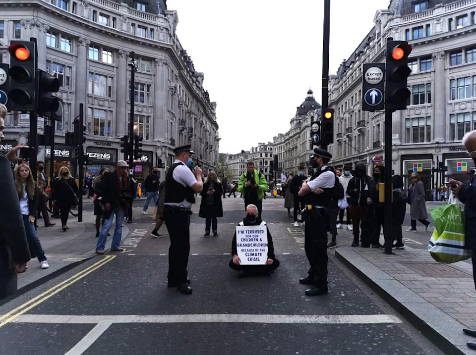 Handout photo taken with permission from the Twitter feed of @dantendles of a protester blocking traffic in Oxford Circus, London, as hundreds of people are staging