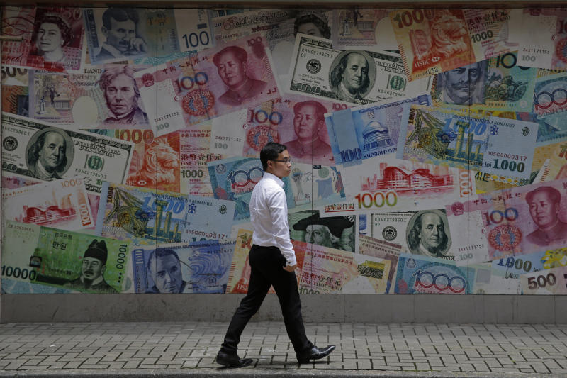 FILE - In this June 10, 2019, file photo, a man walks past a money exchange shop decorated with different banknotes at Central, a business district of Hong Kong.  In a report released Wednesday, Sept. 25, 2019, the Asian Development Bank says that escalating trade tensions will sap Asian economies of some of their potential in this year and the next. (AP Photo/Kin Cheung, File)