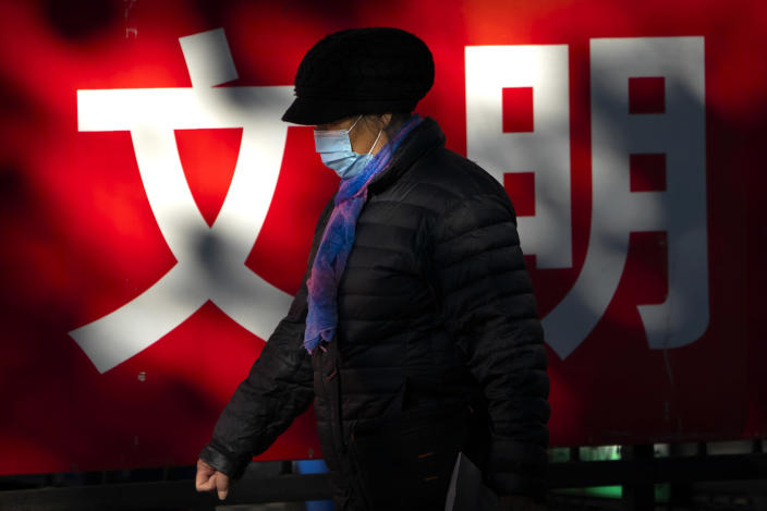 "A woman wearing a face mask to protect against the coronavirus walks past a propaganda billboard with the characters for ""culture"" in Beijing, Friday, Nov. 20, 2020. (AP Photo/Mark Schiefelbein)"