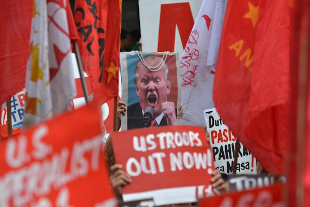 <p>Protesters display anti-US President Donald Trump placards along with his portrait during a rally near the U.S. Embassy, ahead of the 31st Southeast Asian Nations (ASEAN) Summit, in Manila on Nov. 10, 2017. (Photo: Ted Aljibe/AFP/Getty Images) </p>