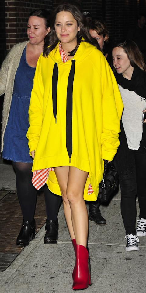 <p>Cotillard hit the streets of New York City in a sunny yellow oversize hoodie and red gingham dress that covered her baby bump. She topped the look off with cherry red cowboy boots.</p>
