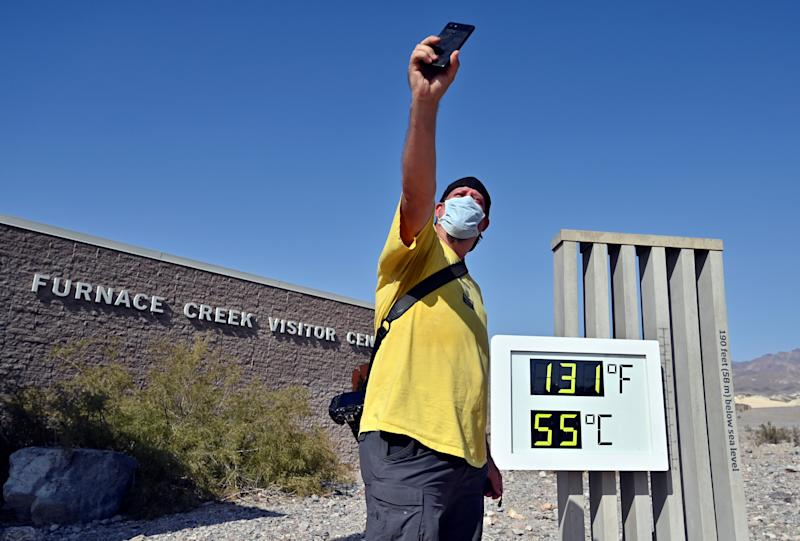 Greg Berndt takes a selfie as the thermometer reads 131 degrees Fahrenheit (55 Celsius) at the Furnace Creek Visitors Center in Death Valley, California.