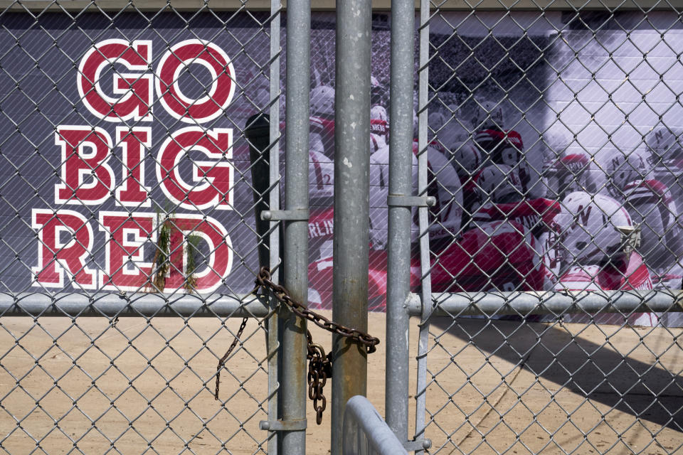 """A chain-link fence is locked ahead of a wall that says """"Go Big Red"""" and a mural of Nebraska football players."""