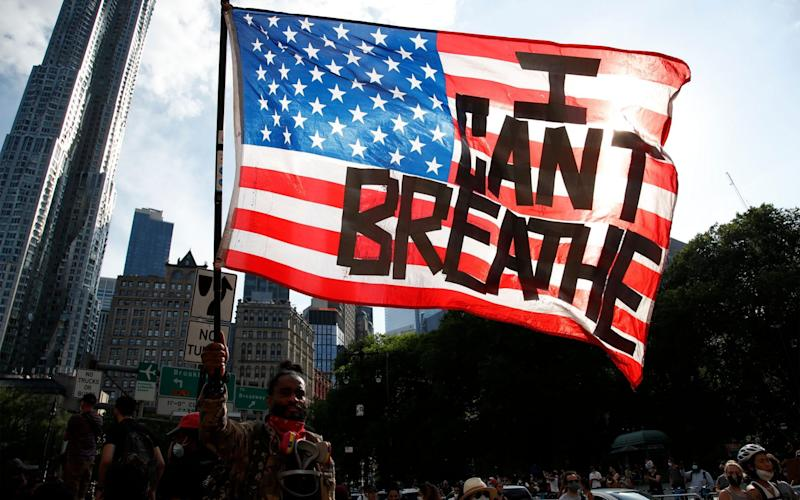 "A protester holds an American flag with the words ""I Can't Breathe"" as he walks in Manhattan after a George Floyd Memorial demonstration in Brooklyn in June - JASON SZENES/EPA-EFE/Shutterstock"