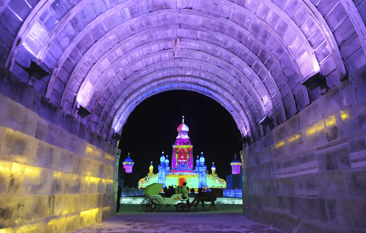 A horse carriage carrying tourists travels past ice sculptures during the lights testing period of the 13th Harbin Ice and Snow World in Harbin, Heilongjiang province December 25, 2011. The Harbin International Ice and Snow Festival will be officially launched on January 5, 2012. Picture taken December 25, 2011. REUTERS/Sheng Li (CHINA - Tags: ENVIRONMENT SOCIETY TRAVEL)