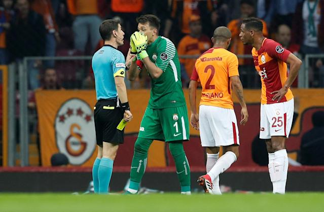 Soccer Football - Turkish Super League - Galatasaray vs Basaksehir - Turk Telekom Arena, Istanbul, Turkey - April 15, 2018 Galatasaray's Fernando Muslera and Fernando remonstrate with referee Halil Meler after Mariano receives a yellow card REUTERS/Murad Sezer