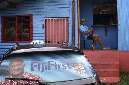 "An election poster for Voreqe ""Frank"" Bainimarama can be seen in the rear window of a taxi as a man gestures from the doorway of a local gymnasium in the Fiji capital of Suva August 26, 2014. REUTERS/Lincoln Feast"