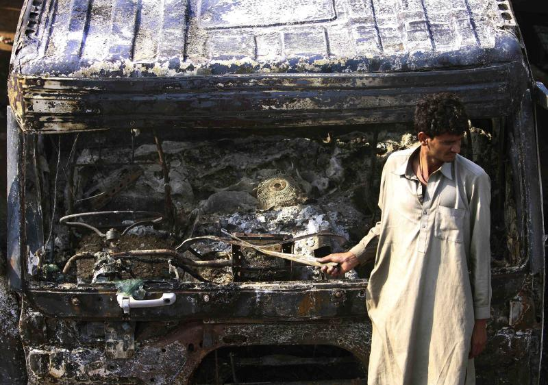 A Pakistani driver stands beside an oil tanker that was attacked by suspected militants at a terminal in Rawalpindi, Pakistan, on Monday, Oct. 4, 2010. Islamist militants attacked and set fire to at least 20 tankers carrying oil for NATO and U.S. troops in Afghanistan on Monday, the third such strike inside Pakistan in as many days, police said. (AP Photo/Aaron Favila)