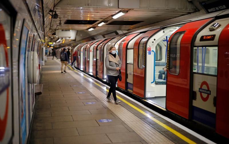 A woman wearing PPE (personal protective equipment), including a face mask as a precautionary measure against COVID-19, walks along the platform alongside a London Underground Tube train, in the morning rush hour on May 11, 2020, as life in Britain continues during the nationwide lockdown due to the novel coronavirus pandemic. - British Prime Minister Boris Johnson on May 10 announced a phased plan to ease a nationwide coronavirus lockdown, with schools and shops to begin opening from June 1 -- as long as infection rates stay low. (Photo by Tolga Akmen / AFP) (Photo by TOLGA AKMEN/AFP via Getty Images)