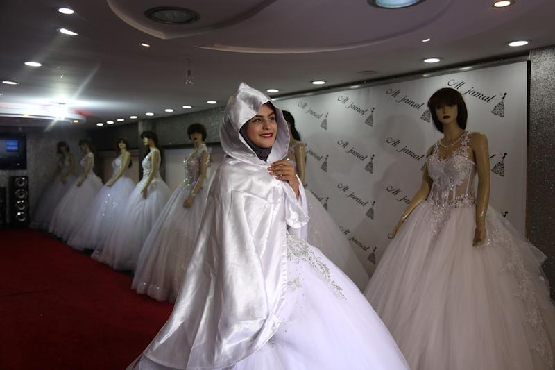 "Hana Abu El-Roos, 18, a Palestinian high school student, tries on a dress as she prepares for her wedding, in a store in Gaza City, Nov. 26, 2018. El-Roos plans to get married this summer but can't find items she needs for her wedding in any of Gaza's shops. ""I haven't picked my wedding dress yet,"" said El-Roos, who is also busy preparing for her final high school exams. ""I am confused. My sisters are helping me."" (Photo: Samar Abo Elouf/Reuters)"