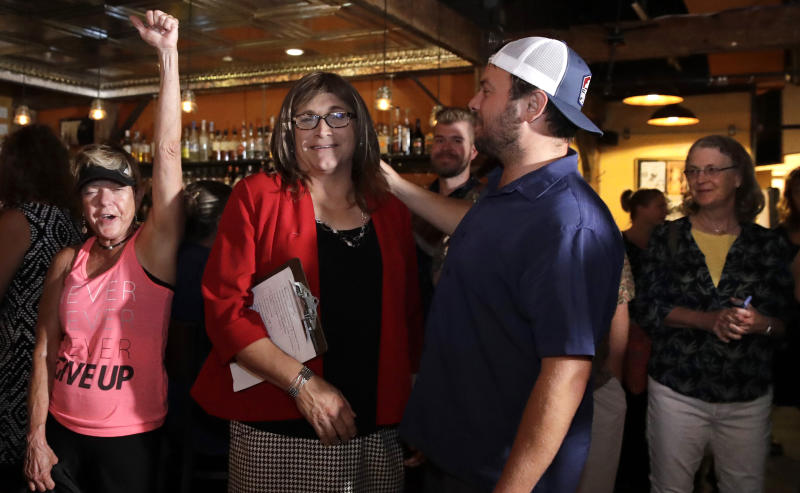 Vermont Democratic gubernatorial candidate Christine Hallquist center a transgender woman and former utility executive is greeted by her supporters during her election night party in Burlington Vt. Tuesday Aug. 14 2018
