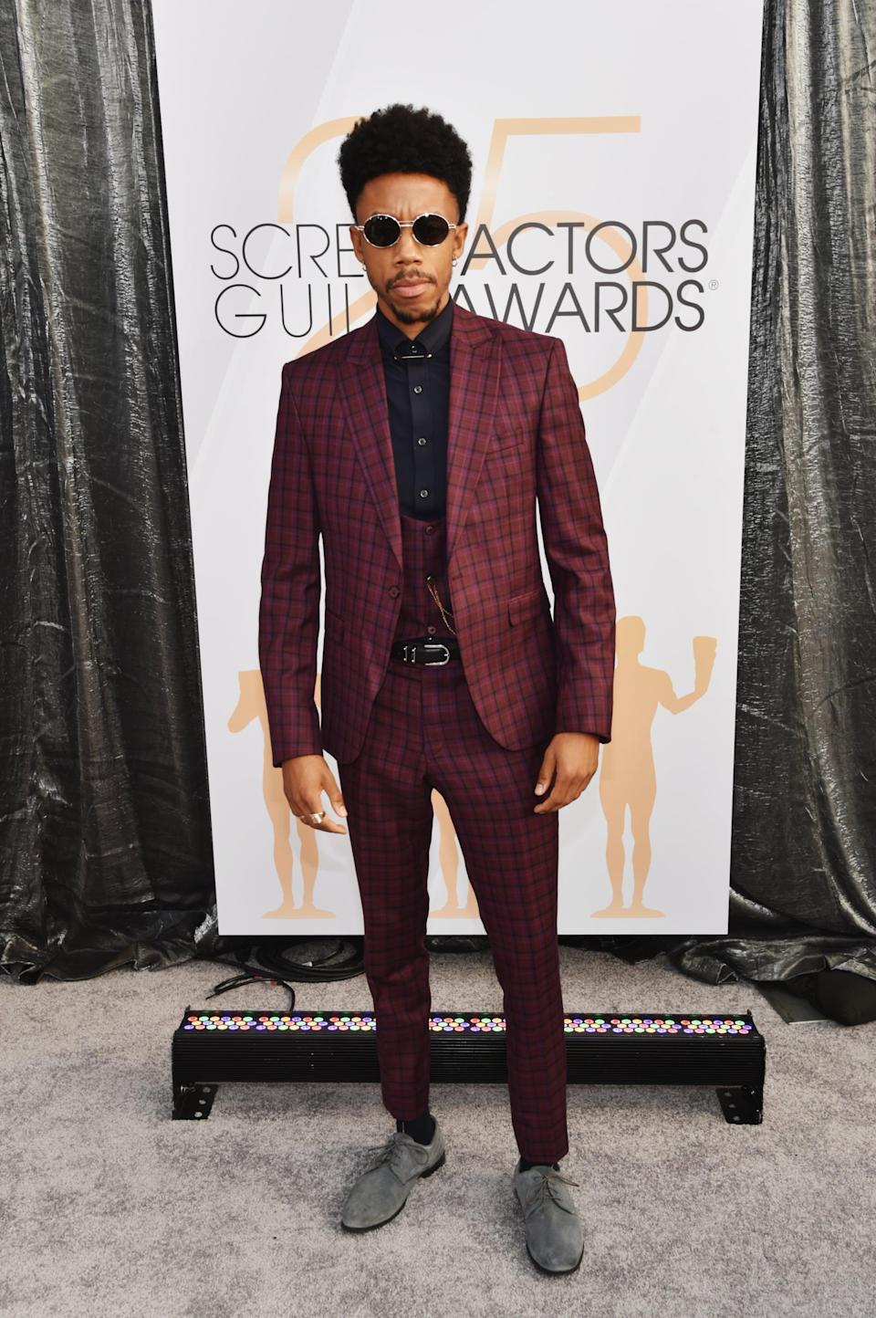 <p>Wearing a burgundy checkered suit. </p>