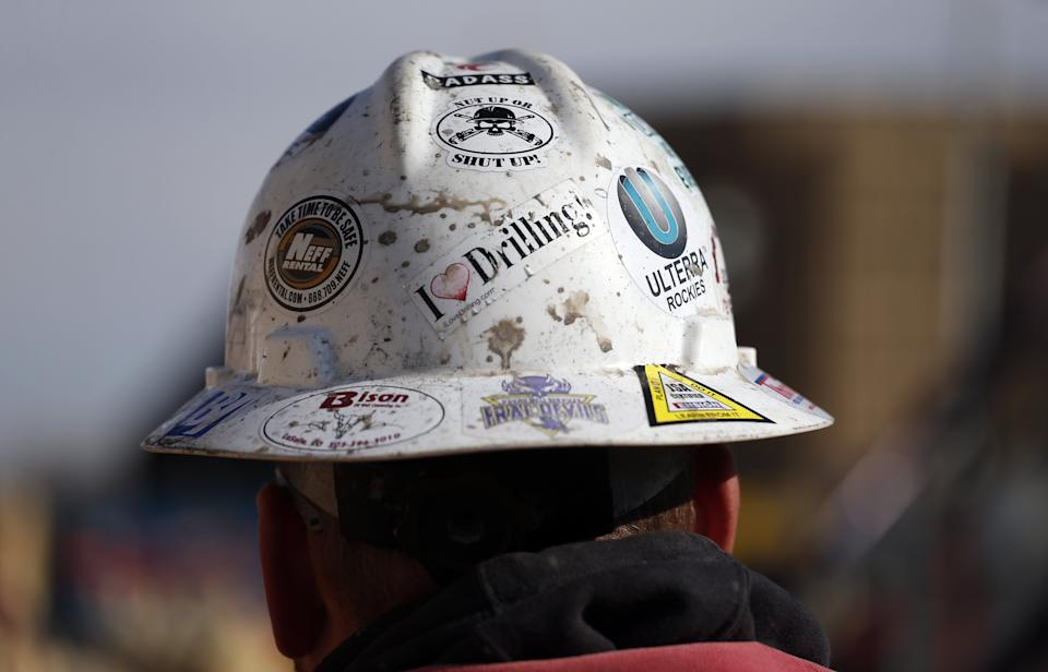 A worker wears a protective helmet decorated with stickers during a hydraulic fracturing operation at an oil well near Mead, Colorado. (Photo: ASSOCIATED PRESS)