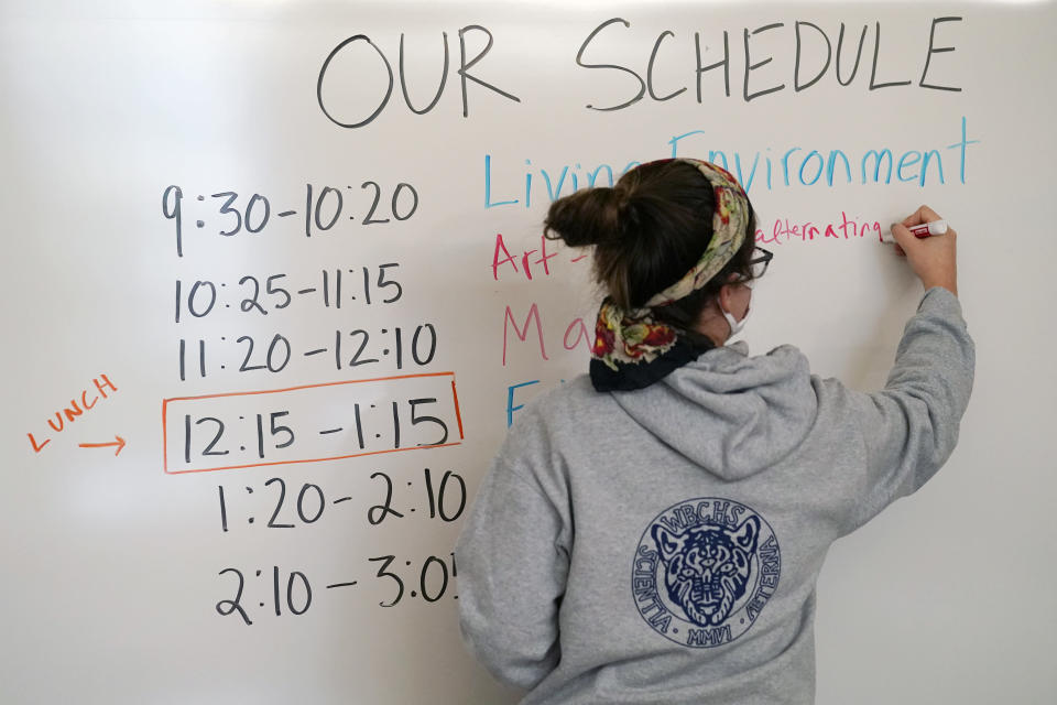 """Global history teacher Alis Anasol writes the schedule on a white board in her classroom at West Brooklyn Community High School, Thursday, Oct. 29, 2020, in New York. The high school is a """"transfer school,"""" catering to students who haven't done well elsewhere, giving them a chance to graduate and succeed. The school is partnered with Good Shepherd Services, who provides advocate counselors to help students achieve their goals. The school, which recently reopened, was forced to shut down for three weeks due to a spike in coronavirus cases in the neighborhood. (AP Photo/Kathy Willens)"""