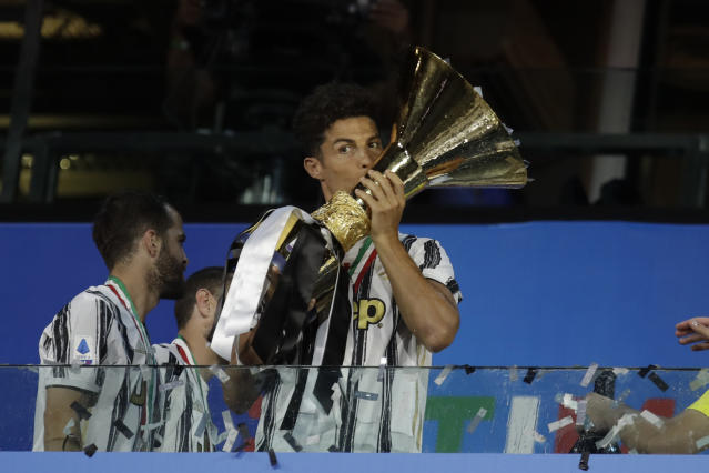 Juventus' Cristiano Ronaldo kisses the trophy as Juventus players celebrate winning an unprecedented ninth consecutive Italian Serie A soccer title, at the end of the a Serie A soccer match between Juventus and Roma, at the Allianz stadium in Turin, Italy, Saturday, Aug.1, 2020. (AP Photo/Luca Bruno)
