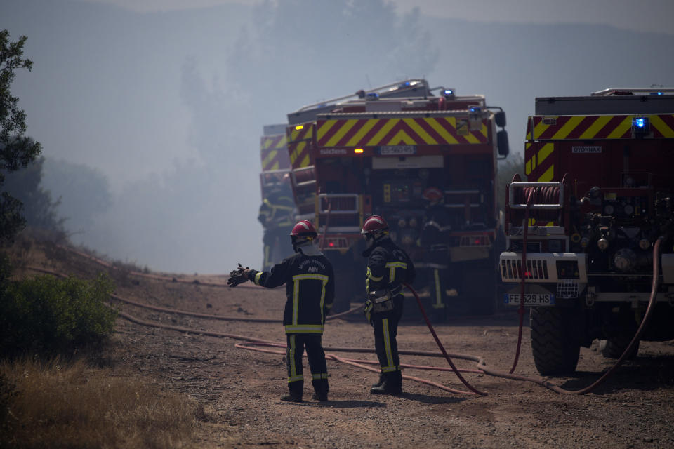Firefighters work at a wildfire near Le Luc, southern France, Thursday, Aug. 19, 2021. A fire that has ravaged forests near the French Riviera for four days is slowing down as winds and hot weather subside, but more than 1,100 firefighters were still struggling to get it under control Thursday, local authorities said. (AP Photo/Daniel Cole)