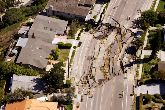 A massive, approximately 200' x 240', sinkhole opens up and tears apart the pavement of Soledad Mountain Road, October 3, 2007 in the Mount Soledad neighborhood of La Jolla near San Diego, California. The landslide has damaged or destroyed reportedly 6 homes and forced the evacuation of at least 20 others. (Photo by Kent Horner/Getty Images)