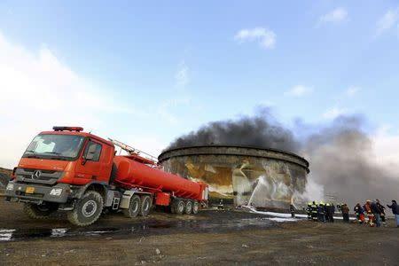Fire-fighters work to put out a fire at a storage oil tank in the port of Es Sider