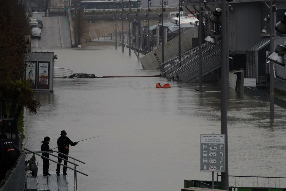 A man and his son fish in the flooded Seine river banks in Paris, Sunday, Feb. 7, 2021. In the Paris region, the Seine River overflowed its embankments for a fifth day. (AP Photo/Christophe Ena)