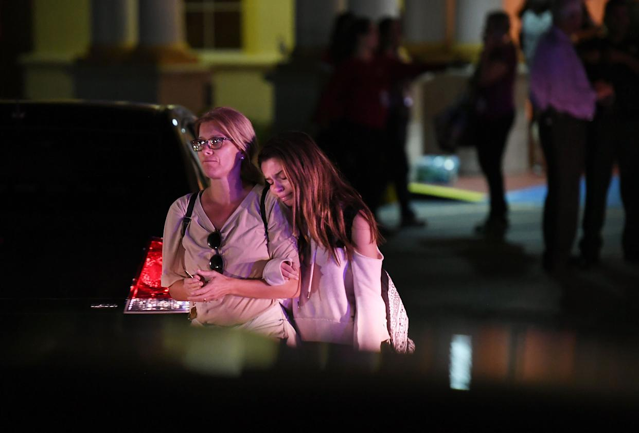 People embrace while leaving the Fort Lauderdale Marriott Coral Springs Hotel after a deadly shooting at Marjory Soneman Douglas High School.